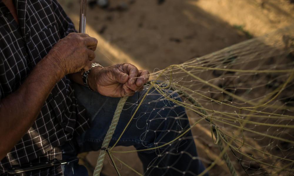 Fishermen mending net