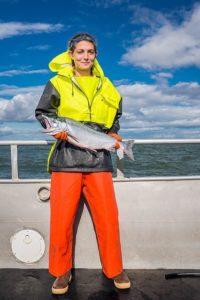 Bristol Bay fisherman holds a bright sockeye salmon.