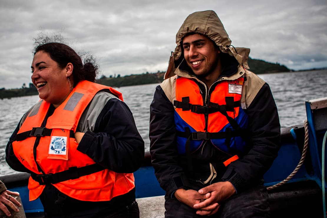 Staff members of AquaChile, the largest exporter of salmon in Chile, work at their marine farm